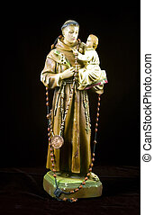 An antinque statuette of Saint Joseph holding baby Jesus isolated on black.