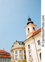 Holy Trinity Roman Catholic Church and city hall at Piata Mare Large Square in Sibiu, Romania