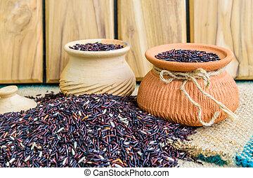 Hom Nil (black jasmine rice) in clay pot on sack wooden ...
