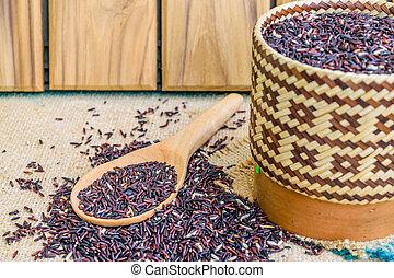Hom Nil (black jasmine rice) in kratip and wooden spoon on ...