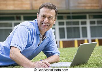 hombre, acostado, en, césped, de, escuela, con, computador portatil