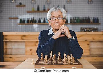 hombre asiático, con, tablero del ajedrez