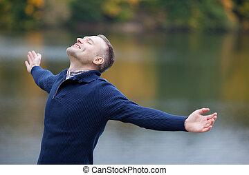 hombre, con, brazos extendidos, al aire libre