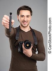 hombre, con, cámara, y, brush., alegre, joven, teniendo cámara, y, cepillo, para, lente, en, el suyo, manos, y, sonriente, mientras, posición, aislado, en, gris