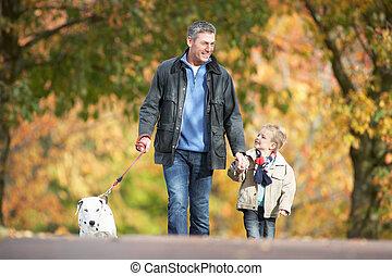 hombre, con, joven, hijo, perro caminante, por, otoño, parque