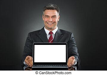 hombre de negocios, actuación, computador portatil, con, pantalla en blanco, en el escritorio