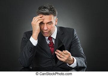 hombre de negocios, con, billetera vacía, sentar escritorio