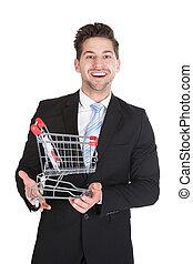 hombre de negocios, con, carro de compras, modelo