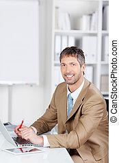 hombre de negocios, con, computador portatil, en, escritorio de oficina
