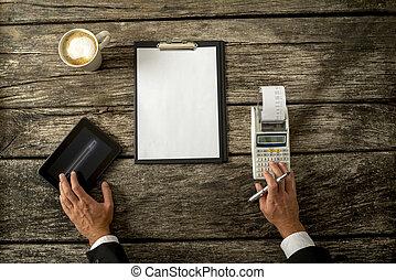 hombre de negocios, con, dispositivos, y, papel, en, tabla