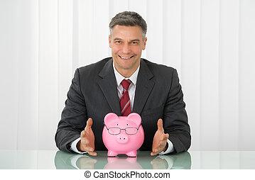 hombre de negocios, con, piggybank rosa, en el escritorio