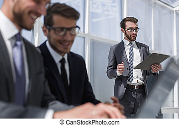 hombre de negocios, con, portapapeles, posición, en, un, moderno, oficina.