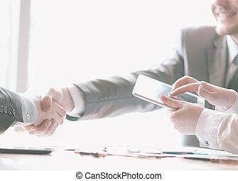 hombre de negocios, con, un, tableta, computadora, en, el, plano de fondo, de, un, apretón de manos, de, socios de negocio