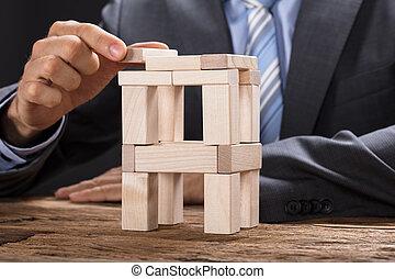 hombre de negocios, edificio, torre, con, bloques de madera