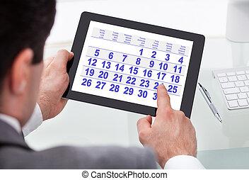 hombre de negocios, el mirar, calendario, en, tableta de digital