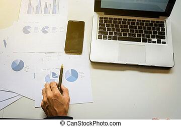 hombre de negocios, mano, trabajando, con, digital, computadora, y, elegante, teléfono, con, empresa / negocio, gráfico, en el escritorio, como, concept.