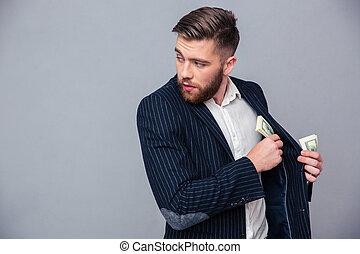 hombre de negocios, poniendo, dinero, en, chaqueta