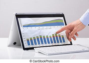 hombre de negocios, señalar, en, el, gráfico, encima, híbrido, computador portatil, pantalla