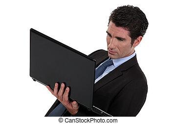 hombre de negocios, se paró, con, computador portatil