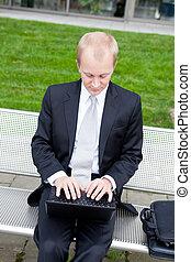 hombre de negocios, sentado, al aire libre, trabajando, con, cuaderno