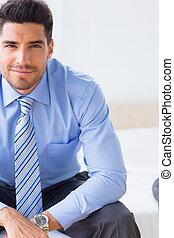 hombre de negocios, sonriente, cámara, cama, sentado
