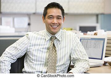 hombre de negocios, sonriente, cubículo