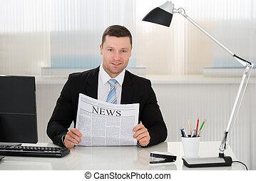 hombre de negocios, sostener el periódico, en el escritorio, en, oficina