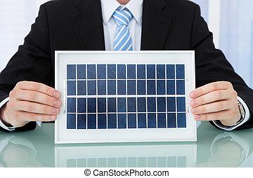 hombre de negocios, tenencia, panel solar, en, escritorio de oficina