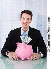 hombre de negocios, tenencia, piggybank, en el escritorio