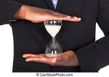 hombre de negocios, tenencia, reloj de arena