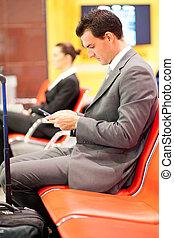 hombre de negocios, transmitir, o, lectura, mensajes del texto, en, aeropuerto