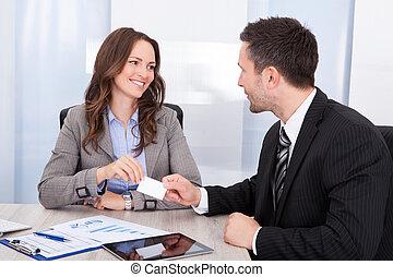 hombre de negocios, y, mujer de negocios, cambiar, tarjeta visitante, en, escritorio de oficina