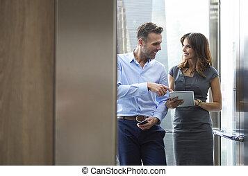 hombre de negocios, y, mujer, en, el, elevador