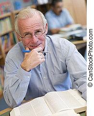 hombre, en, biblioteca, con, pluma y, libro, (selective, focus)