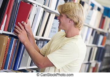 hombre, en, biblioteca, tirar, libro, de, un, estante, (depth, de, field)