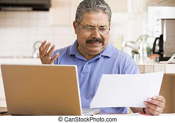 hombre, en, cocina, con, computador portatil, y, papeleo,...