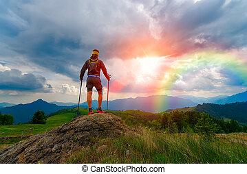hombre, en las montañas, en, ocaso, con, arco irirs