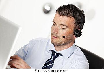 hombre en oficina, con, auriculares, y, computadora