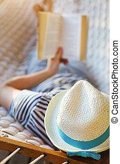 hombre en sombrero, en, un, hamaca, con, libro, en, un, día de verano