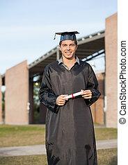 hombre, en, traje de ceremonia de entrega de diplomas, tenencia, diploma, en, campus de la universidad