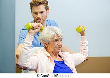 hombre, entrenador, entrenamiento, mujer anciana, con, dumbbells, en, centro de la aptitud
