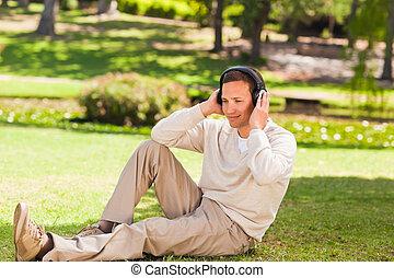 hombre, escuchar música, en el parque
