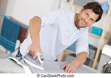 hombre, hierro ropa, planchado, feliz