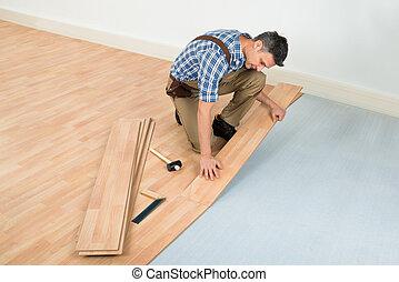 hombre, instalación, nuevo, laminado, piso de madera