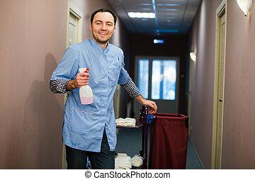 hombre, limpieza, hotel, vestíbulo, llevando, abrigo azul