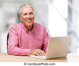 hombre maduro, trabajo encendido, computador portatil