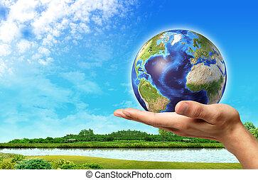 hombre, mano, con, globo de la tierra, en, él, y, un, hermoso, paisaje verde, con, río, y azul, cielo, en, fondo.
