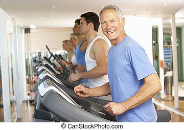 hombre mayor, en, máquina corriente, en, gimnasio