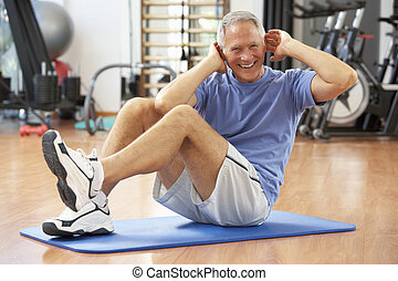hombre mayor, hacer, sit ups, en, gimnasio