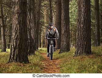 hombre, practicar, montaña biking, en, el, bosque